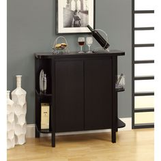 Make entertaining easier with this wood bar unit. Two doors lead to storage space for your liquor and other beverages, and the top provides you a surface on which to serve your guests. With its lovely cappuccino finish, this piece matches any decor.