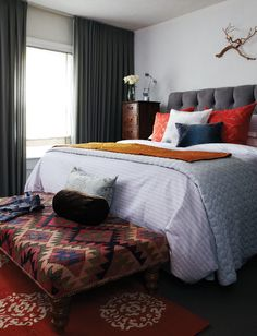 In designer Karen Cole's bedroom, two mismatched tall found cabinets stand on either side of the bed and act as storage units for socks and delicates. A large kilim-upholstered ottoman, layered atop a