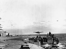 Black and white photograph of a single engined monoplane flying just above the deck of an aircraft carrier with its wheels extended. Two oth...