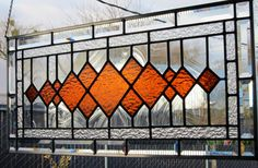I handcrafted this beautiful stained glass window panel using textured amber glass surrounded by a background of baroque glass. An inner border of textured glass highlighted by an outer border of bevels completes the design. This window measures 31 9/16 inches by 13 9/16 inches. There are 4 hangers soldered into each corner so that the window can be hung vertically or horizontally. This stained glass window panel is made of leaded glass. It is not copper foil. The panel is sea...