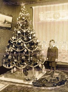 A little boy in short pants stands beside a beautifully decorated antique Christmas tree with train set Old Time Christmas, Large Christmas Tree, Old Fashioned Christmas, Christmas Past, Victorian Christmas, Christmas Holidays, Christmas History, Christmas Lights, Antique Christmas Decorations