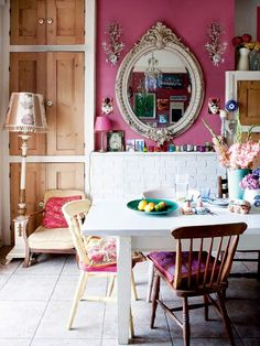 A dark pink wall sets off an ornate mirror and sconces, while the white fireplace and table keep the room from feeling too busy. #dining