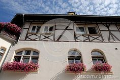 Photo taken in a center called Bacharach along the Rhine valley in Germany. In the picture you see the white facade of one of the typical houses with wooden logs in the upper part of the wall on which open window with flower plants in the balcony. Four other small windows open at the top below the pitch of the roof outlined by the sky with small white clouds.