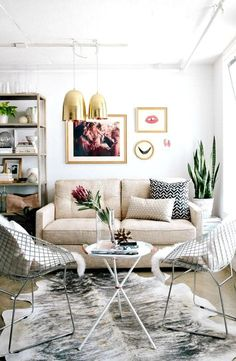 small living room with cowhide rug and gold brass pendants and gold framed wall art