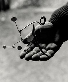 ALEXANDER CALDER, Calder holding one of his miniature mobile sculptures, Saché, France 1963. Photograph by Ugo Mulas. / Palazzo Esposizioni