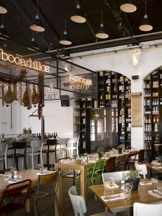 Mixed chairs, white walls, dark ceiling, wood accents. typography on metal mesh above bar,