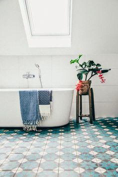 The Moroccan inspired floor tiling makes this all-white bathroom look a lot more interesting