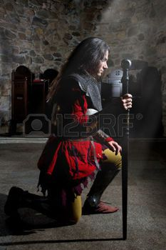 armor sword: Side View of Knight in Armor With Sword Praying in the Old Church