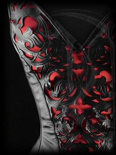 Bodice detail of overbust corset with straps, featuring a gothic styled ornamentation and red satin inlay.