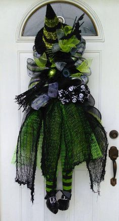 Created by Wreaths by Rita - https://www.facebook.com/wreathsbyrita This stunning Wicked Witch wreath is over 4ft in height. She is made up of a pencil garland, black metallic mesh, silver, black and green striped mesh, silver wide foil 10in mesh all materials from www.trendytree.com. To finish her off I added a big hat in which I added a little flair to, some different ribbons, a raz broom (TT), extra layer to skirt and green and black striped legs. #trendytree