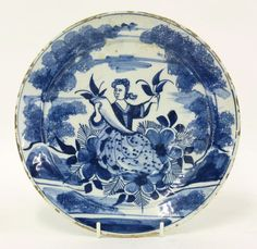 A London delft Plate, early 18th century, in Dutch style with Flora grasping a turnipoid cornucopia beneath sponged trees, Jo mark,    22cm