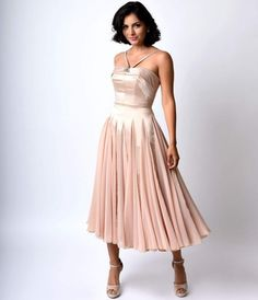 Let the divine drama commence, dames! A refined retro inspired dress exclusive to Unique Vintage, The Dovima is a sumptuous ballerina style swing in a sleek champagne satin and chiffon fabrication. A glittering brooch adorned statement neckline supports a