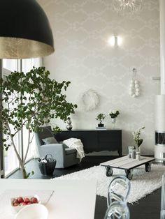 Ruokailutilasta näkyy olohuoneeseen, jossa Behangwereld.nl-nettikaupasta hankittu tapetti rikkoo korkean tilan kauniisti. Senkki on Ikeasta, nojatuoli HT Collectionin Swing, joka ostettiin Vepsäläiseltä. Valkoinen nukkamatto on Askosta ja kuminen säilytyskori Ojan Raudasta. Sanna on askarrellut seinällä olevan koristepalloketjun styrox-palloista. Sohvapöytä on Mikon tekemä. Takka on Linnatulen Wilma, joka on maalattu kuultavalla, metallinhohtoisella helmiäislasyyrillä.
