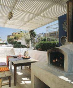 As arquitetas Denise Abdalla e Christiane Sacco idealizaram um amplo pergolado com estrutura de alumínio e ripas de madeira para abrigar a churrasqueira e o forno de pizza em formato iglu Construflama.