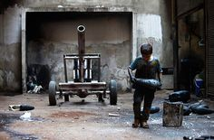 Credit: Hamid Khatib /Reuters Aleppo, Syria: A ten-year-old boy named Issa carries a mortar shell in a factory making weapons for the Free Syrian Army