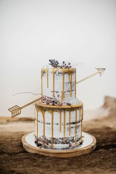 36 Drip Wedding Cakes Almost Too Pretty To Eat. Whimsical drip cake with arrow. See more at http://www.theweddingguru.ca/36-drip-wedding-cakes-almost-too-pretty-to-eat/ #dripcake