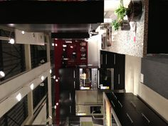 Ikea kitchen - dark shelves. open cabinets that are high contrast red. white countertop. under cabinet lighting. island. and light floors