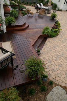 Large platform deck designed with diagonal floor board pattern and built with center steps leading to the patio. | Fine Decks Inc. | houzz.com