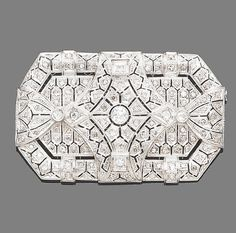 A diamond plaque brooch  The pierced plaque collet-set to the centre with three brilliant-cut diamonds, within a single-and brilliant-cut diamond surround, diamonds approx. 3.45ct. total, length 7.1cm. Late Edwardian or early Art Deco or in the style thereof