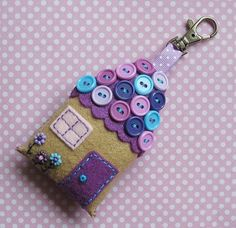 Key ring made from felt in the design of a housee, and decorated with buttons for the roof