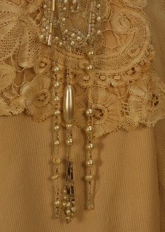 "Detail PARIS BEADED SILK and LACE EVENING GOWN, c. 1914. Beige silk having striped pattern weave, boned bodice in net with short sleeve, bobbin lace, and net pendant bands with pearls and crystal beads ending with pearl drops, draped and gathered narrow skirt with self bows and buttons, side lace insert and pearl drops, Petersham (detached) stamped ""Chellier,"