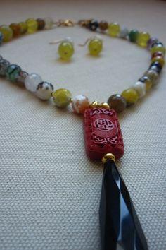Juego de collar pegado al cuello y aretes realizado con agatas craqueladas, amarillas y agata negra facetada, con pieza de resina tallada , accesorios en chapa de oro.