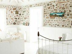 1-salon-avec-mur-en-pierre-de-parement-intérieur-et-sol-en-planchers-clairs-lit-en-fer