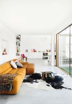 Loftartiges Wohnen mit hellem Betonboden und bunter Einrichtung