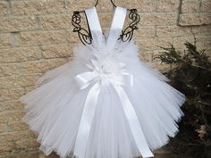 Baby Pure White, tutu dress, christening gown, baptism dress, flower girl, birthday photo shoots, special blessing, white tutu dress, girls tutu dress, baby gifts. Available in baby and toddler sizes.  The dress has a stretchy, crochet-like bodice, which stretches to 22 inches around the chest for the lengths 14, 16, and 18 inches. It stretches to 26 around the chest for the 20, 22, and 24 inch lengths. All sizes are approximate. It has a bit of fluff around the top and a row of fluff all…