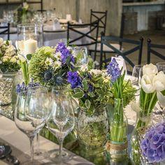 Arreglo floral con hortensias malva, tulipan blanco y velas sobre espejo. El Campillo + Mar de Flores