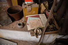 Treasure trove: Empty gas cannisters lie next to piles of paperwork and bits of rubble inside the basement station