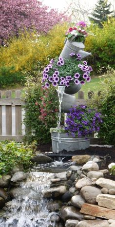 Cute fountain made out of metal buckets and watering cans.