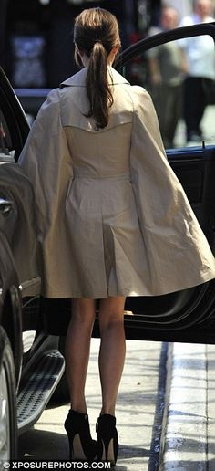 Caped crusader: The fashion designer looked chic in the Burberry number, which she paired with a pair of black boots