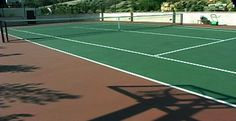 Lovely green tennis court with a brown surround.