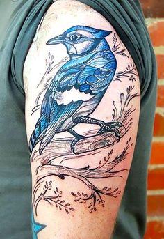 A beautiful tattoo of a bluebird sitting on a branch. Color: Blue. Tags: Cool, Beautiful