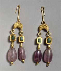 Gold earrings composed of a filigree-decorated crescent from which is suspended a pair of box-set gems of opaque green glass and pendant amethysts, dating to the sixth century.