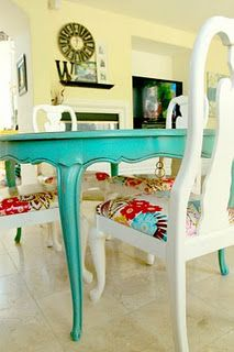 Turquoise table, white chairs with great print on the chair seats.