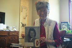 Grace Amemiya, 95, holds a photo of her as a U.S. Cadet Nurse Corps during World War II, on Thursday, Aug. 18, 2016. This Saturday Amemiya will be inducted into the Iowa Women's Hall of Fame. Photo by Grayson Schmidt/Ames Tribune