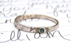 A tiny blue fair trade sapphire gemstone is set in recycled silver in a simple, stackable style~