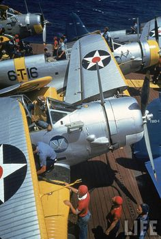 Crewmen from the USS Enterprise (CV-6) servicing Douglas TBD-1 Devastators during maneuvers off the coast of Hawaii in September 1940. These planes are from Torpedo Squadron Six (VT-6).