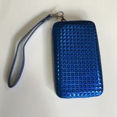 NWOT Shiny blue wristlet wallet/phone case combo NWOT It's all-in-one!! Shiny blue squares decorate the outside of this multi-function bag. The black interior has a spot for your phone, ID, 2 other cards, and a pocket for your cash. The clear window on one side allows you to use your phone without opening the case! Snap closure. NOT waterproof! The strap is removable for use as a clutch or wallet. I used mine at DisneyWorld and it was PERFECT!! This is a back-up I purchased and have never…