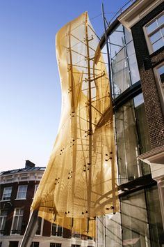 De Baljurk - Kettingstraat. A golden three-dimensional wire cloth dress for the facade made of HAVER Architectural Mesh.