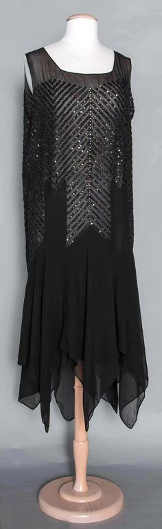 Evening dress ca. late 1920s. Black silk chiffon, handkerchief hem, rows of black beads & sequins in chevron patterns, sleeveless. Suddon-Cleaver Costume Collection. Augusta Auctions.