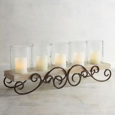 Hand-carved wood and graceful wrought iron scrollwork create a stylish centerpiece to showcase a set of five glass pillar candle holders. Wrought Iron Candle Holders, Unique Candle Holders, Unique Candles, Pillar Candle Holders, Candle Stand, Candle Sconces, Pillar Candles, Candleholders, White Candles