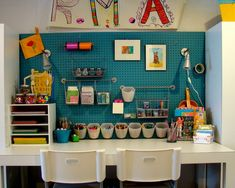 If we decide to create the kids' space in office against a wall, I love the idea of painting peg board in a bright color and hanging all the art supplies.  Use a cheap IKEA desk in front of the pegboard.