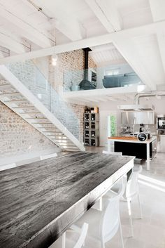 All white modern loft with exposed brick. Love the polished wood and steel dining room table
