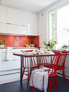 Nice use of RED tile splashback and chairs in a white kitchen.