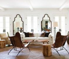 A light-filled living room has an appealing global vibe. Twin Moroccan mirrors add an exotic look to the space.