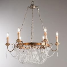 "Crystal Draped Iron Chandelier Crystal beads drap this gold leaf iron chandelier creating an elegant antique inspired look. The traditional drapped beaded bottom basket attaches to a distressed gold leaf iron frame and carved wood arms. This well-dressed chandelier sparkles with old world style. 6x60 watt candle base lamps max. (35""Hx31""W)"