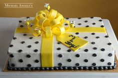 Baby Bee & Bow #51Baby This sheetcake is iced in buttercream with black polka dots all over. Yellow fondant ribbon is placed on the cake to look like a present. The fondant bow and bees make this cake look festive for any celebration.